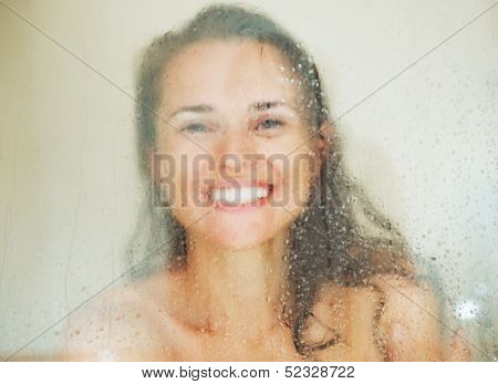 Smiling Young Woman Behind Weeping Glass Shower Door