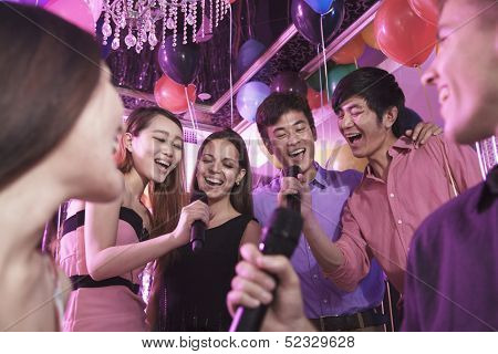 Group of friends holding microphones and  singing together karaoke