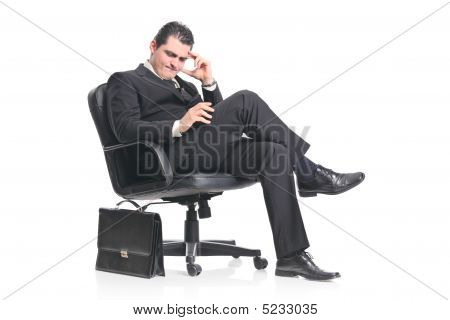 A Worried Businessman Sitting In An Office Chair