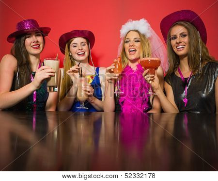 Laughing friends having hen party holding cocktails looking at camera