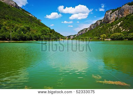 Lake And Blue Sky With Clouds Between The Mountains