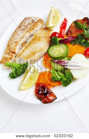 Fresh hake filet with grilled vegetables in a seafood restaurant