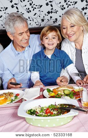 Happy little child eating with his grandparents at the dinner table