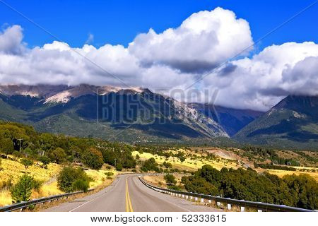 Patagonia. The longest road the Ruta 40 passes in Argentina among lakes and fields. Magnificent cumulus clouds decorate mountains of the Southern Andes