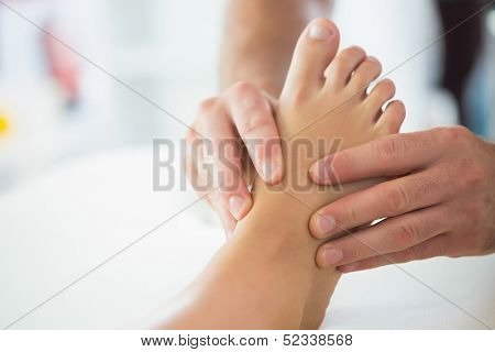 Close up of physiotherapist massaging patients foot in bright office