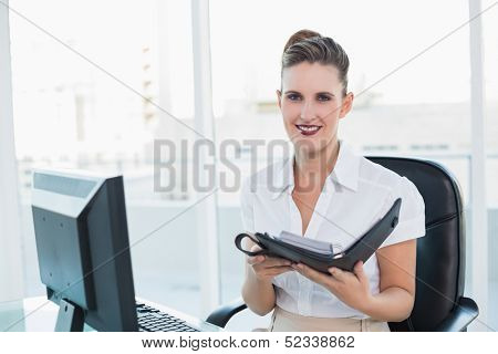 Smiling woman holding her datebook looking at camera