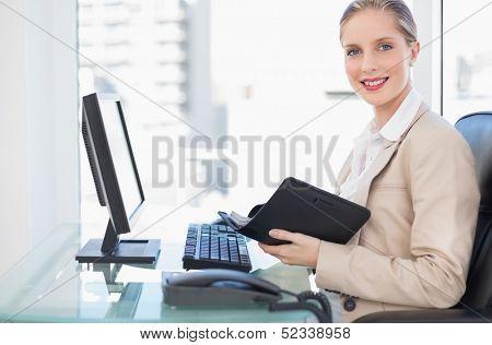 Cheerful blonde businesswoman in bright office holding datebook