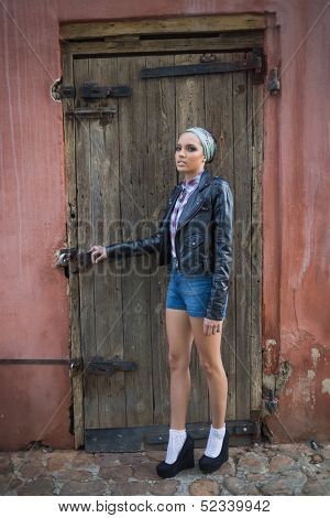 Attractive woman with hairband posing and looking at camera in front of a wooden door