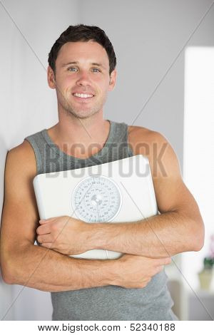 Sporty smiling man leaning against wall holding a scale in bright room