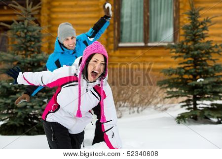 Cute couple having fun outdoors during winter holidays and playing at snowballs