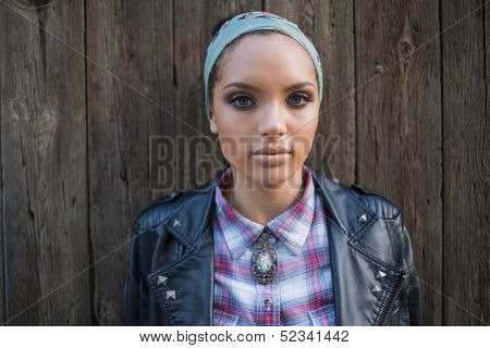 Close up of attractive woman with hairband looking at camera in front of a wooden door