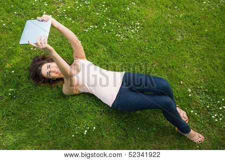 Happy young woman lying on a lawn using her tablet on a sunny day