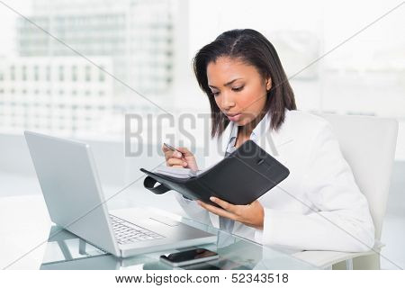 Anxious young dark haired businesswoman filling her schedule in bright office