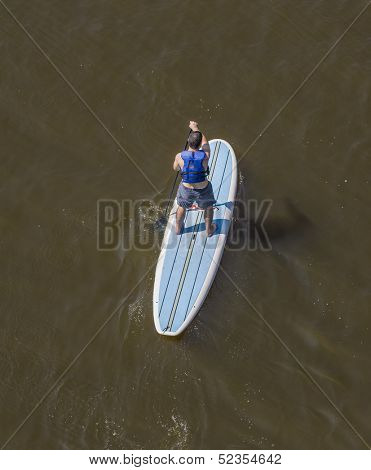 male from behind paddling a paddleboard on river