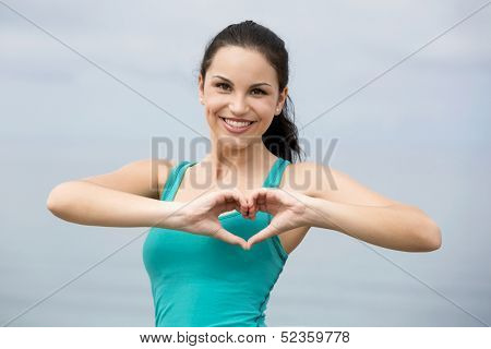 Beautiful young woman in outdoor doing a heart shape with her hands