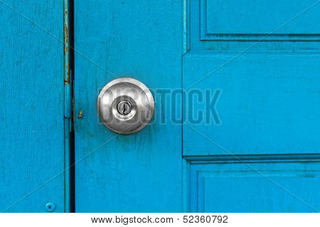 Blue old door with silver door knob.