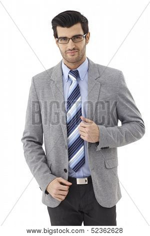 Portrait of confident young businessman in suit and glasses.