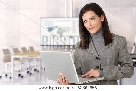 Young businesswoman holding laptop preparing for presentation in meeting room.