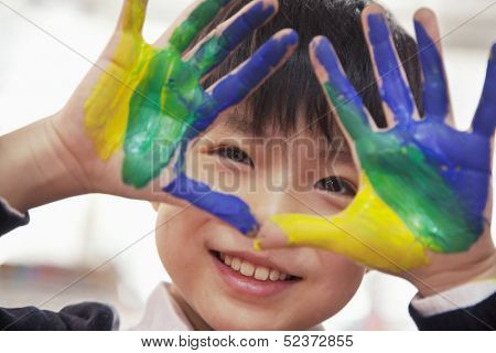 Portrait of smiling boy with fingers painted