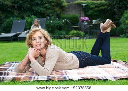 Attractive Mature Woman Relaxing In Garden