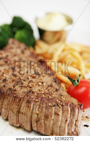 Close up of a steak served with broccoli and french fries