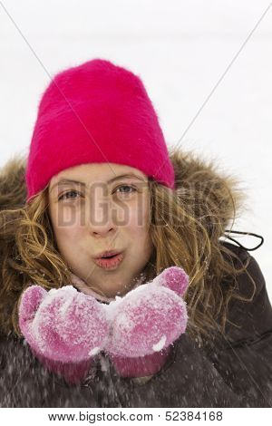 Young teenager with pink tuque blowing fresh snow in the air