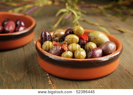Varitey of olives into into bowls on wooden table