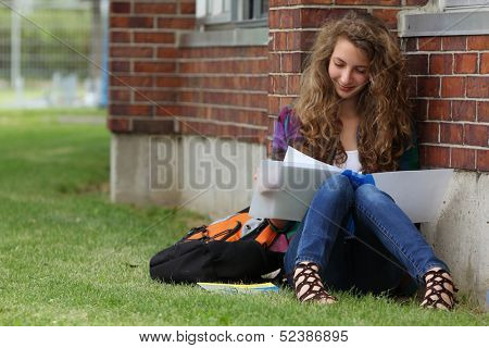 Smiling girl sit on a grass outside and study her lessons