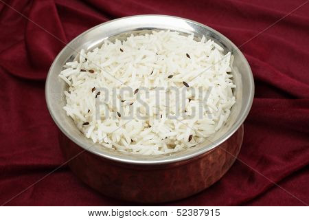 Jeera rice - long-grain basmati rice flavoured with fried cumin seeds - in a beaten copper and steel serving bowl