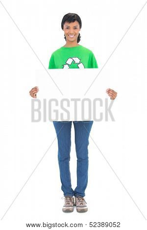 Pleased black haired ecologist holding a white panel in front of her on white background