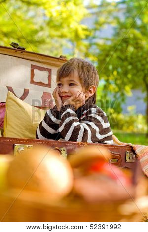 Smiling Little Boy Sitting In A Suitcase
