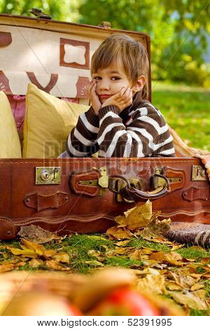 Sad Little Boy Sitting In An Old Suitcase