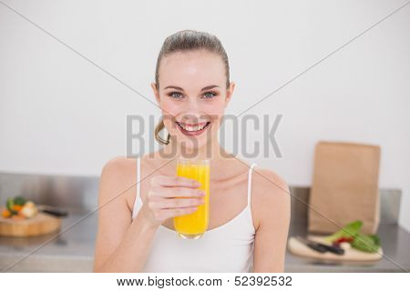 Happy young woman holding glass of orange juice in the kitchen at home