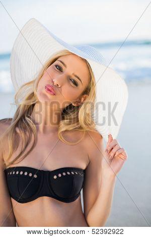 Pretty sensual blonde in elegant black bikini wearing straw hat on a beautiful sunny beach