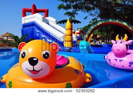 Inflatable Toys In Children Sweeming Pool And Inflatable Castle On Background. Beach On Seacost, Bud