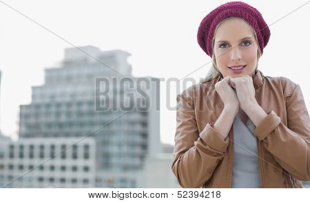 Shivering casual blonde posing outdoors on urban background