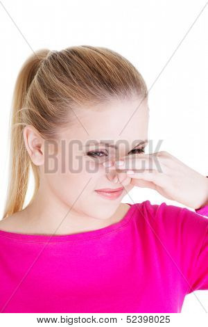 Woman covers nose with hand showing that something stinks, isolated on white