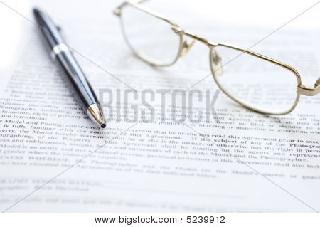 Close-up Of Document, Eyeglasses And Pen.