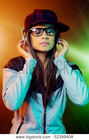 Portrait of trendy woman listening to music on headphones hiphop fashion