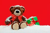 A handmade teddy bear sitting in the snow with gift wrapped Christmas presents against a red backgro