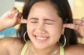 picture of filipina  - a filipina plugs here ears so she can