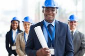 stock photo of blue-collar-worker  - handsome african male architect holding blue print and team - JPG