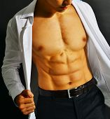pic of nipple  - Muscular and tanned male torso isolated on black background - JPG