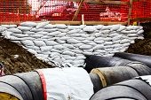 pic of sandbag  - White sandbag bags are full with sand in wall formation to hold the Earth near traffic road - JPG