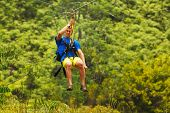 Man on Zipline over Lush Tropical Valley