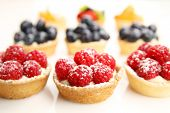 Assortment of fruity tarts on white background