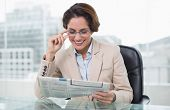 Smiling businesswoman reading newspaper at her desk in bright office