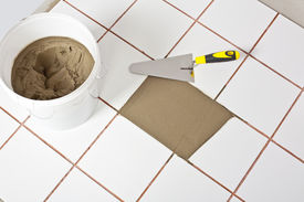 foto of mortar-joint  - Trowel and old white tiles with tile adhesive bucket - JPG