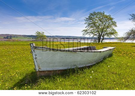 An old weathered rowboat resting in the grass along the shore of rural Prince Edward Island, Canada.
