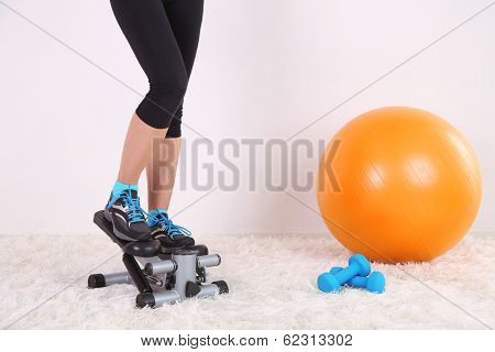 Young beautiful fitness girl exercising on stepper in gym